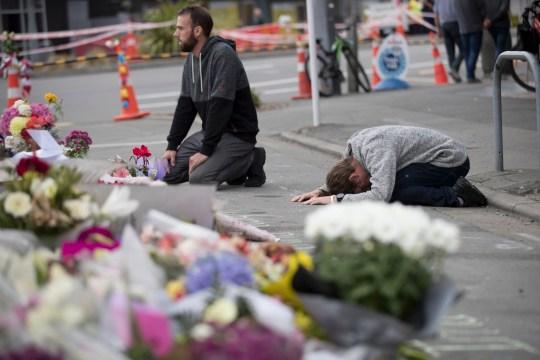 DOSSIER - Dans cette photo d'archive du 19 mars 2019, des personnes en deuil prient près de la mosquée Linwood à Christchurch, en Nouvelle-Zélande.  Plus de 60 survivants et membres de la famille affronteront le tireur de la mosquée néo-zélandaise au cours de la condamnation de quatre jours à compter du lundi 24 août 2020. L'Australien Brenton Harrison Tarrant, 29 ans, a plaidé coupable à 51 chefs de meurtre, 40 des chefs de tentative de meurtre et un chef de terrorisme dans la pire atrocité de l'histoire moderne du pays (AP Photo / Vincent Thian, File)