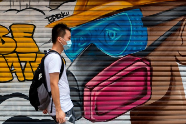 A man wearing a face mask as a precautionary measure against the COVID-19 coronavirus walks on a street in Hong Kong on August 23, 2020. (Photo by May JAMES / May James / AFP) (Photo by MAY JAMES/May James/AFP via Getty Images)