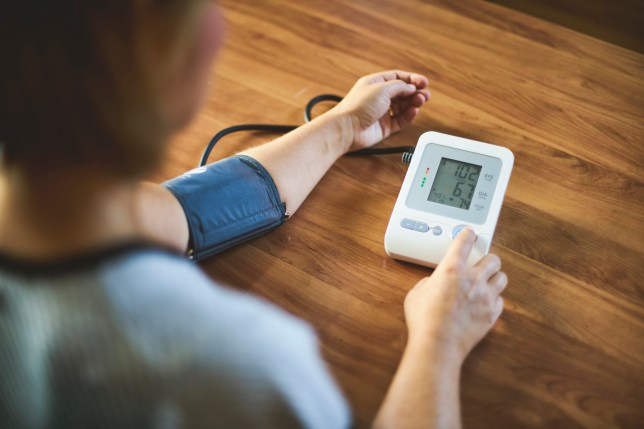Woman using medical device to measure blood pressure