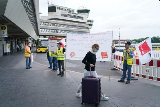BERLIN, ALLEMAGNE - 19 JUIN: Un voyageur passe devant des travailleurs de l'aéroport qui protestent à l'aéroport de Tegel contre les paiements de congé de pandémie de coronavirus qu'ils prétendent être insuffisants le 19 juin 2020 à Berlin, en Allemagne.  Le personnel au sol des aéroports protestent aujourd'hui dans les aéroports du pays pour ce qu'ils prétendent être une interprétation mal appliquée des calculs de Kurzabeiter pour les paiements.  Dans le cadre du système allemand Kurzarbeit, les travailleurs mis à pied en raison des conséquences de la pandémie ont reçu jusqu'à 80% ou plus de leur salaire.  Les équipages de l'aéroport disent que leurs paiements n'incluent pas les heures supplémentaires et les heures de nuit de leur salaire de travail régulier, ce qui signifie qu'ils ont été rémunérés avec une part beaucoup plus petite de leur salaire net normal.  (Photo par Sean Gallup / Getty Images)