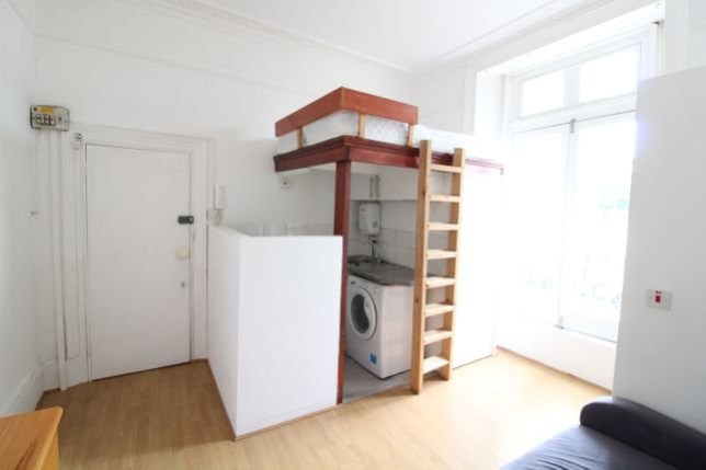 The inside of the tiny flat with the bed  visible above the small kitchen, which is next to the toilet.