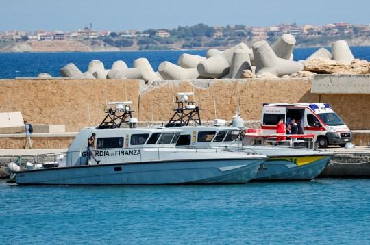 Les services d'urgence et Guardia di Finanza sont vus sur le quai du Castella après qu'un bateau de migrants a pris feu lors d'opérations de sauvetage au large de Crotone, avec des personnes toujours portées disparues selon les médias italiens, Italie le 30 août 2020.