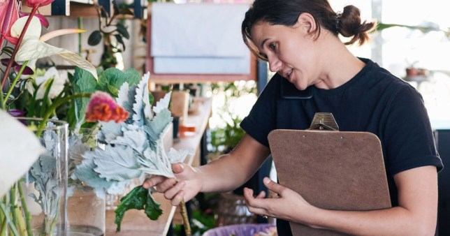 A florist examines her stock.