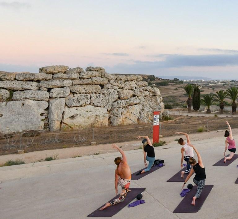 doing yoga against the gozo hills backdrp[