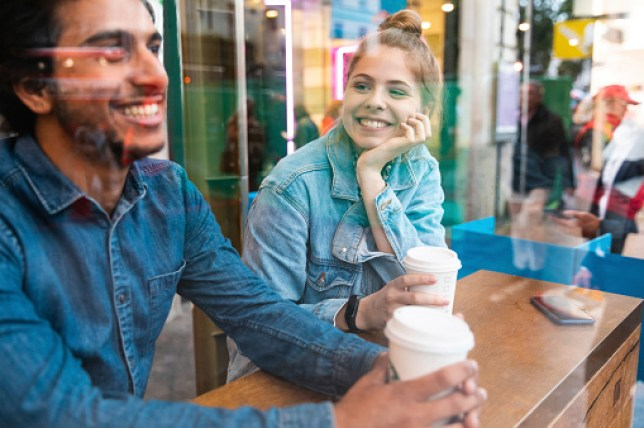 Portrait of smiling young woman in a coffee shop looking at young man