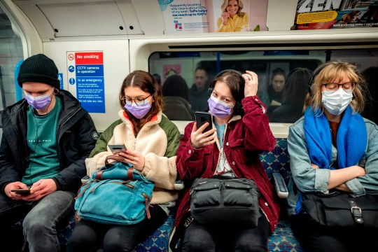 Commuters wear masks while travelling on a London Underground