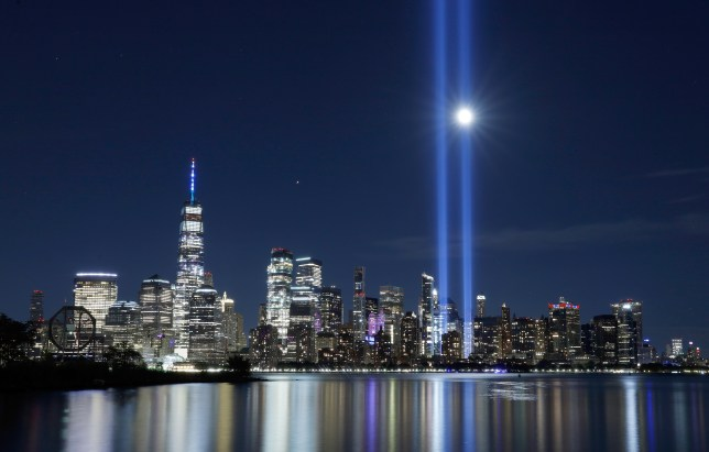 The moon rises behind a beam of the Tribute in Light as it is tested over lower Manhattan and One World Trade Center in New York City.