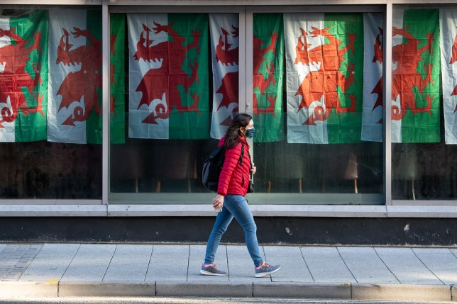 A woman wearing a face covering walks past a venue with Wales flags hanging in their window.