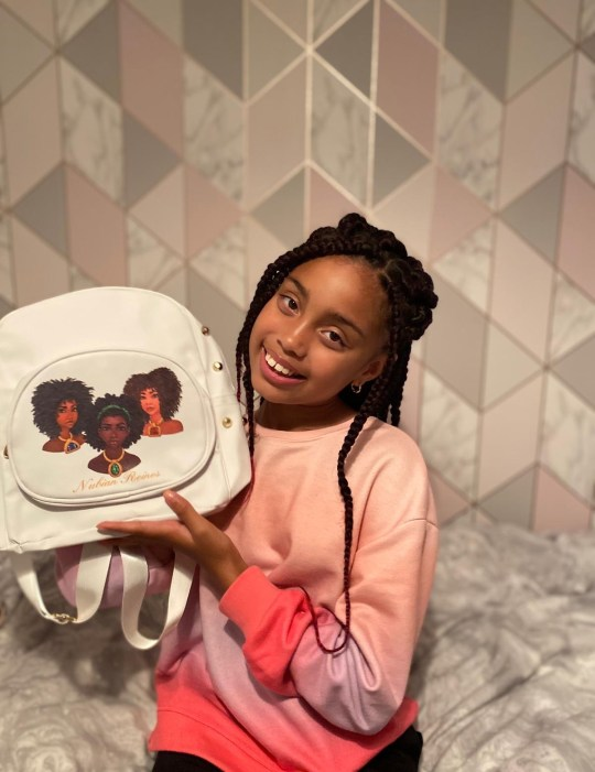 A young black girl holding a three black princess backpack