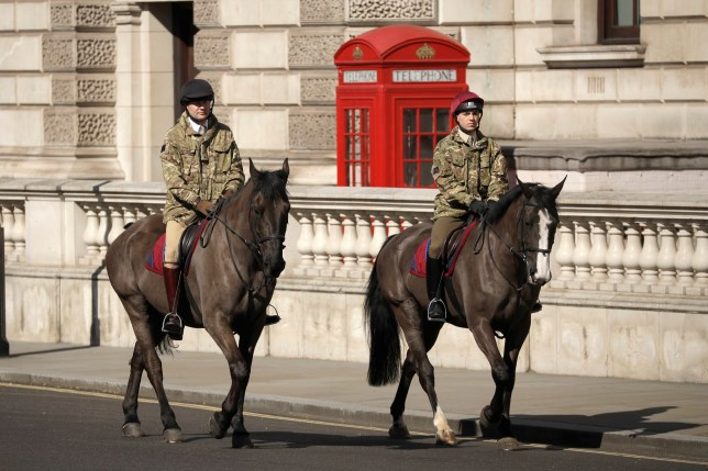 Two members of a British Army mounted regiment exercise their horses in Parliament Square, in London, Wednesday, March 25, 2020, British lawmakers will vote later Wednesday to shut down Parliament for 4 weeks, due to the coronavirus outbreak. The new coronavirus causes mild or moderate symptoms for most people, but for some, especially older adults and people with existing health problems, it can cause more severe illness or death.(AP Photo/Matt Dunham)