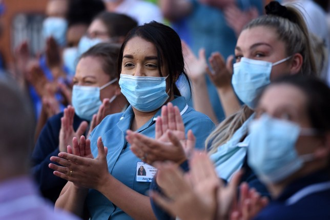 Members of staff of the Leeds General Infirmary participate in a national NHS (National Health Service) celebration clap outside the hospital in Leeds on July 5, 2020, to mark its 72nd anniversary. - This year's celebration is particularly poignant given the challenging conditions NHS staff have had to work under over the past four months amid the coronavirus outbreak. (Photo by Oli SCARFF / AFP) (Photo by OLI SCARFF/AFP via Getty Images)