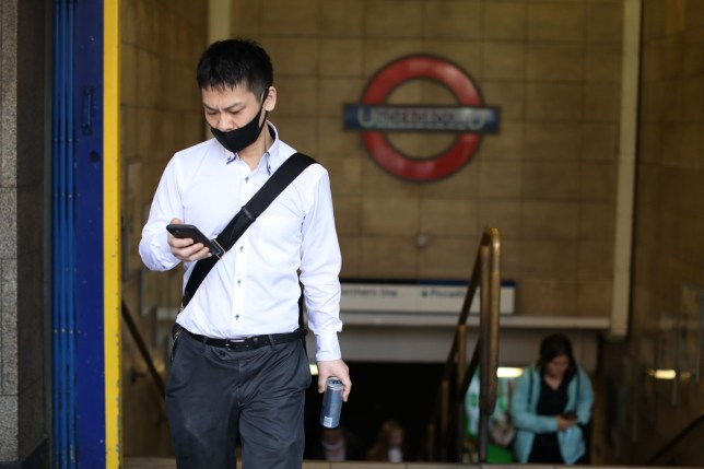 A man wearing a face mask as a precaution against the spread of the novel coronavirus climbs the steps to the street from Leicester Square