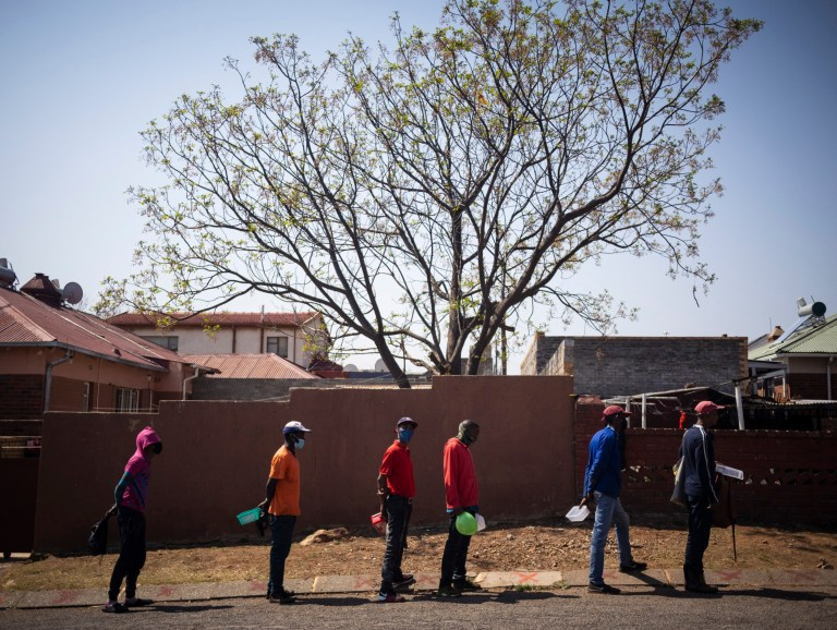 People wait in line during a food handout on day 160 of the national lockdown as a result of Covid-19 Coronavirus, in Johannesburg, South Africa