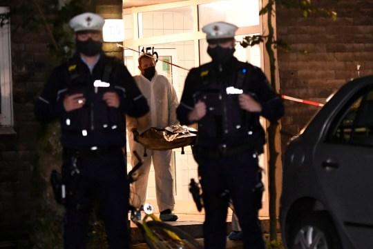 Des employés d'une société funéraire portent un cadavre à un corbillard sous la protection de policiers, jeudi 3 septembre 2020, à Solingen, en Allemagne.  La police affirme que cinq enfants ont été retrouvés morts dans un appartement d'une ville de l'ouest de l'Allemagne et que leur mère est soupçonnée de les avoir tués.  Les corps de trois filles et de deux garçons ont été retrouvés jeudi à Solingen, près de Cologne et de Düsseldorf.  La police a déclaré que la mère de 27 ans des enfants avait sauté plus tard devant un train à Düsseldorf et avait été emmenée à l'hôpital avec des blessures.  (Roberto Pfeil / dpa via AP)