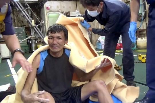 Dans cette image réalisée à partir d'une vidéo publiée par le 10e quartier général régional des garde-côtes japonais, un membre d'équipage secouru d'un cargo panaméen est assis, enveloppé dans une couverture, chez des membres de la Garde côtière japonaise, au large d'Amami Oshima, au Japon, mercredi 2 septembre 2020 Les sauveteurs japonais ont arraché en toute sécurité le membre d'équipage de la mer tout en recherchant le cargo transportant plus de 40 membres d'équipage et des milliers de vaches ont disparu après avoir envoyé un appel de détresse au large de l'île du sud du Japon.  (Le 10e quartier général régional des garde-côtes japonais via AP)