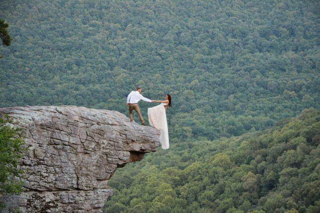 Skye and Ryan Myers holding hands on the edge of a cliff on their wedding day