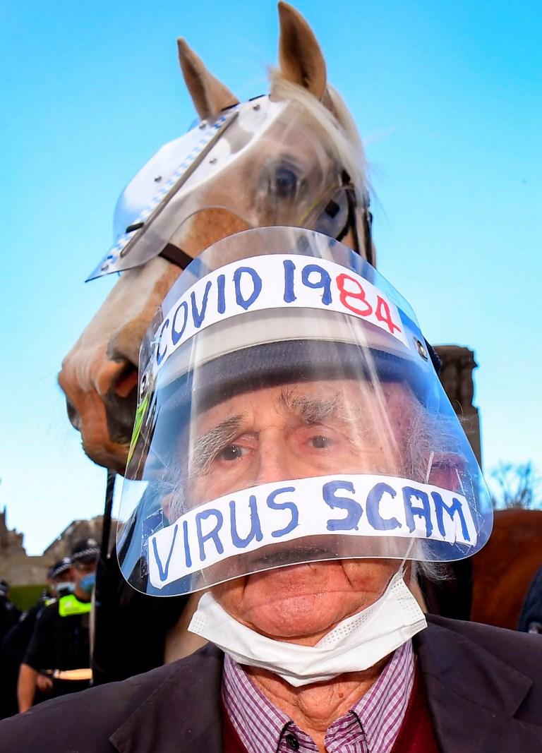 Un manifestant confronte la police au sanctuaire du souvenir à Melbourne avec un écran facial qui se lit comme suit: `` Covid 1984 / Virus Scam ''