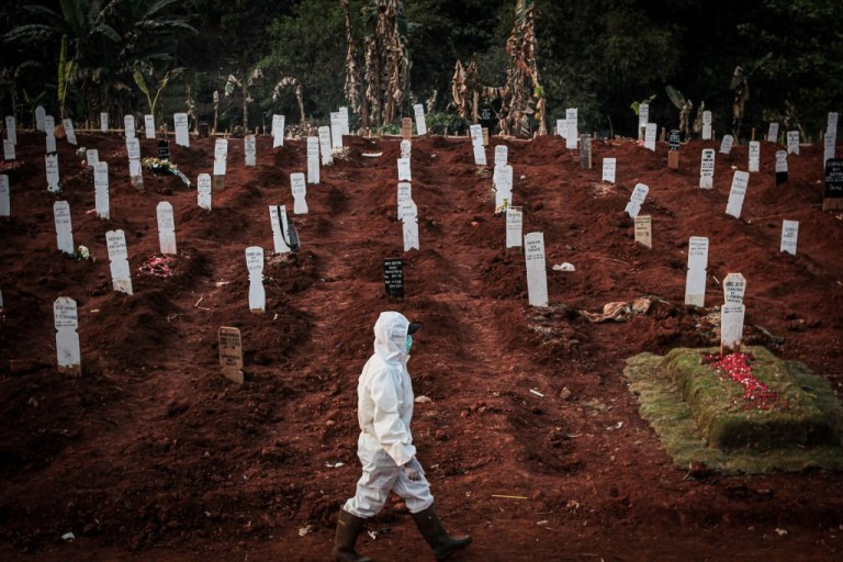 An officer wearing a hazmat suit walks in front of the grave of a coronavirus victim at the public burial ground in Pondok Rangon, Cipayung, East Jakarta City. Indonesia