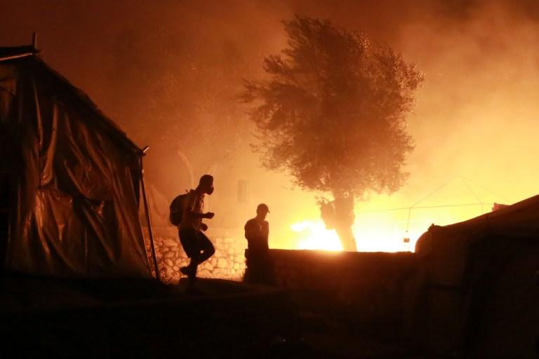 Des migrants marchent à l'intérieur du camp de Moria sur l'île de Lesbos lors d'un incendie majeur le 9 septembre 2020.