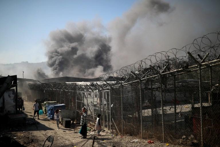 Des réfugiés et des migrants sont vus parmi des abris détruits à la suite d'un incendie dans le camp de Moria sur l'île de Lesbos, en Grèce, le 9 septembre 2020.