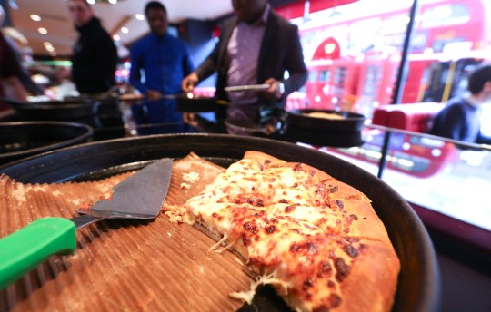Customers select pizza slices from the pizza buffet table inside a Pizza Hut restaurant, owned by Yum! Brands Inc., at the company's flagship restaurant on The Strand in London, UK. on Tuesday, March 24, 2015.