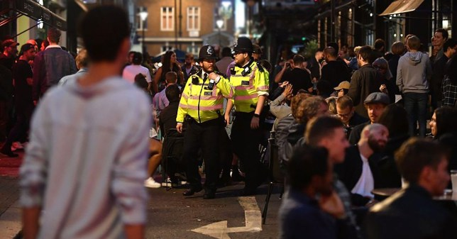 Police officers patrol as revellers crowd the street outside bars in the Soho area of London on July 4, 2020, as restrictions are further eased during the novel coronavirus COVID-19 pandemic. - Pubs in England reopen on Saturday for the first time since late March, bringing cheer to drinkers and the industry but fears of public disorder and fresh coronavirus cases. (Photo by JUSTIN TALLIS / AFP) (Photo by JUSTIN TALLIS/AFP via Getty Images)