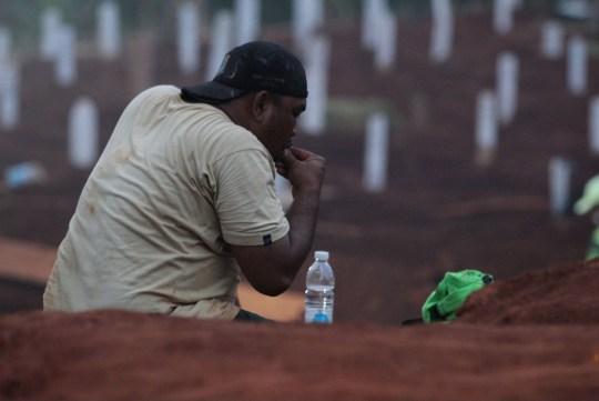 Crédit obligatoire: Photo de Kuncoro Widyo Rumpoko / Pacific Press / REX (10774079aw) Un officier funéraire pour le corps d'un patient covid-19 se repose dans une zone spéciale pour les corps des victimes du covid-19 au cimetière public de Pondok Rangon, à l'est de Jakarta , 11 septembre 2020. Alors que le nombre de résidents exposés à de plus en plus de victimes a reculé, le nombre de terriers laissés pour les corps des patients de Covid-19 sur ce site funéraire n'est que d'environ 1 100 terriers.  Le gouvernement provincial de la région spéciale de la capitale de Jakarta augmentera également la capacité de charge pour l'inhumation des corps des patients COVID-19 sur les terres de ce cimetière public.  Funérailles des patients Covid-19 à Pondok, Jakarta, région spéciale de la capitale de Jakarta, Indonésie - 11 septembre 2020