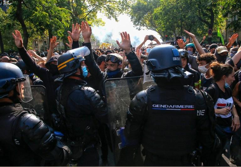 Des manifestants gilets jaunes portant des masques protecteurs par mesure de précaution contre le conoravirus lèvent la main lors d'une marche à Paris, samedi 12 septembre 2020.