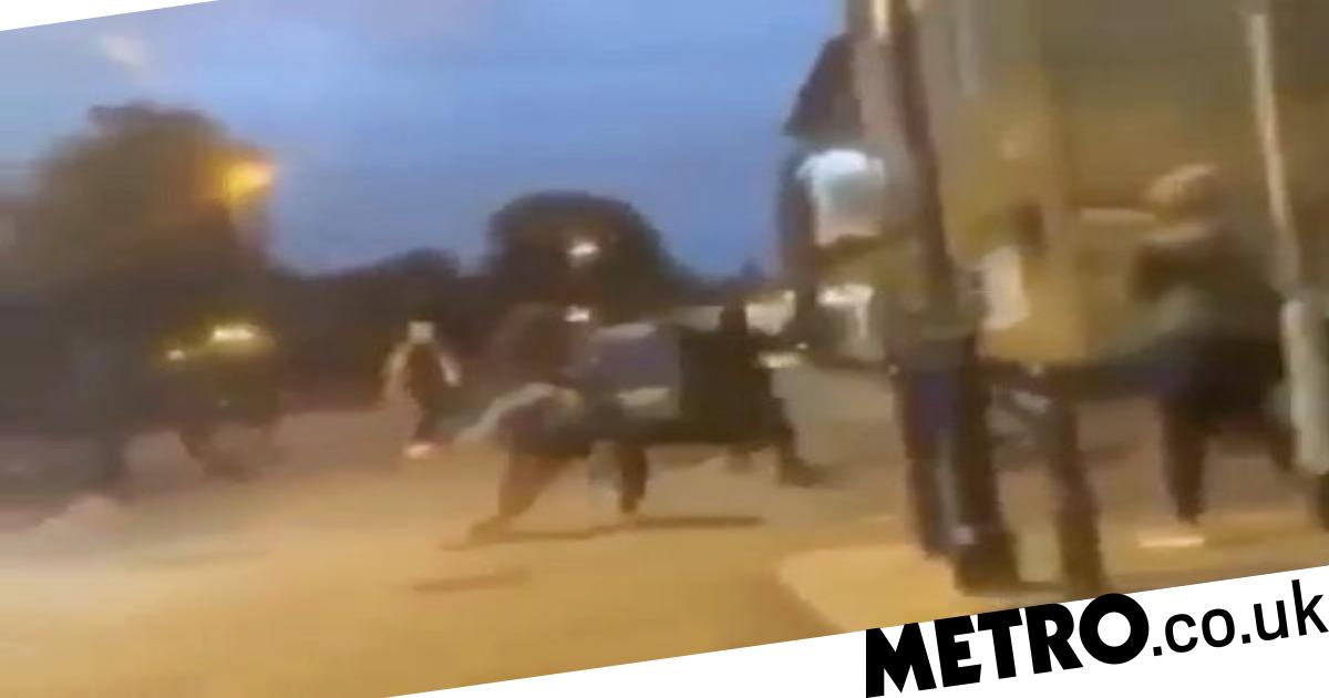 Men fight with bats and broom handles during mass street brawl - metro