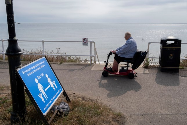 A disabled man drives his mobility scooter past a social distance sign on the seaside promenade, during the Coronavirus pandemic, on 14th August 2020, in Southwold, Norfolk, England.