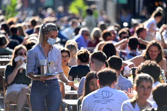 A waitress wearing a protective face covering brings drinks to customers in the late summer sunshine at outside tables in Soho, central London on September 20, 2020 as the British government consider fresh nationwide restrictions after an rise in cases of the novel coronavirus.