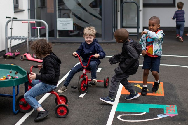 LONDON, ENGLAND - JUNE 04: Children maintain social distancing measures as the play in the playground at the Harris Academy's Shortland's school on June 04, 2020 in London, England. As part of Covid-19 lockdown measures, Harris Academy schools have taught smaller pods of students, to help maintain social distancing measures. With restrictions now lifting and the Government encouraging schools to re-open, the school staff has been working to find the best way to provide extra spaces while still retaining the correct social distancing measures and cleanliness requirements. This week, some schools across England reopened for some students, with children in reception, Year 1 and Year 6 allowed to return first. (Photo by Dan Kitwood/Getty Images)