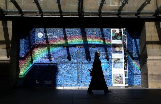 The changing face of the high street. A woman walks past a Rainbows for the NHS mosaic made up of thousands of pictures and stories, submitted during the ongoing pandemic, which covers the windows and entrance to the Buchanan Galleries in central Glasgow, some six months on from the evening of March 23 when Prime Minister Boris Johnson announced nationwide restrictions. PA Photo. Issue date: Wednesday September 23, 2020. See PA story HEALTH Coronavirus. Photo credit should read: Andrew Milligan/PA Wire