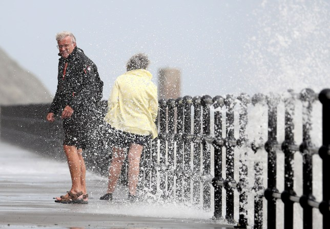 A couple are splashed by waves crashing over the promenade in Folkestone, Kent. Strong winds are expected to sweep across the UK ahead of the weekend, bringing the potential for travel disruption and flooding.