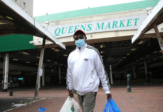 A man wearing a protective face mask walks out of an almost-empty Queens Market in Upton Park, east London, as the UK continues in lockdown to help curb the spread of the coronavirus. Picture date: Tuesday April 28, 2020.