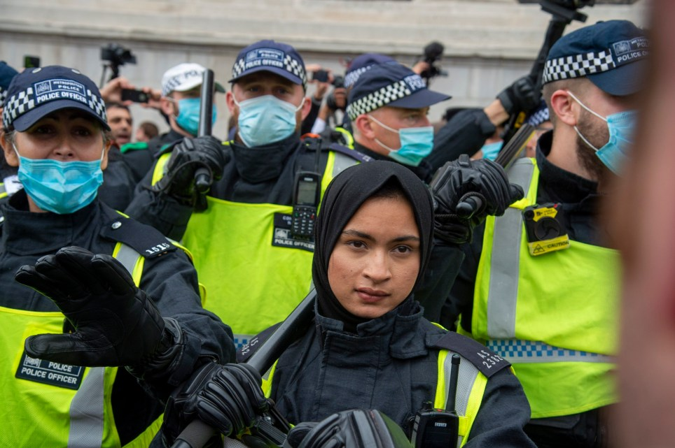 Police officer in a hijab and without a face mask, holding a baton during the demonstration. The officer became the target of racist and Islamophobic abuse online after her picture was shared