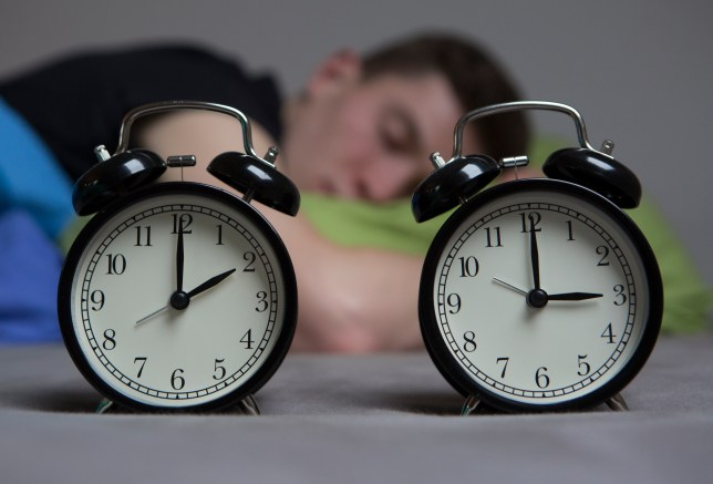 Man sleeping next to two clocks an hour apart.