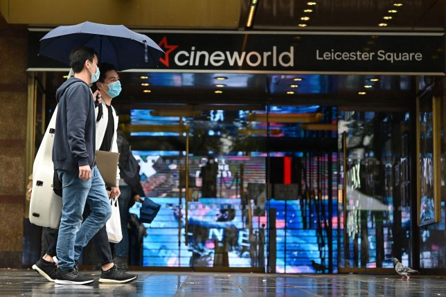 Passers-by shelter from the rain under an umbrella, walk past a cineworld cinema in Leicester Square in central London