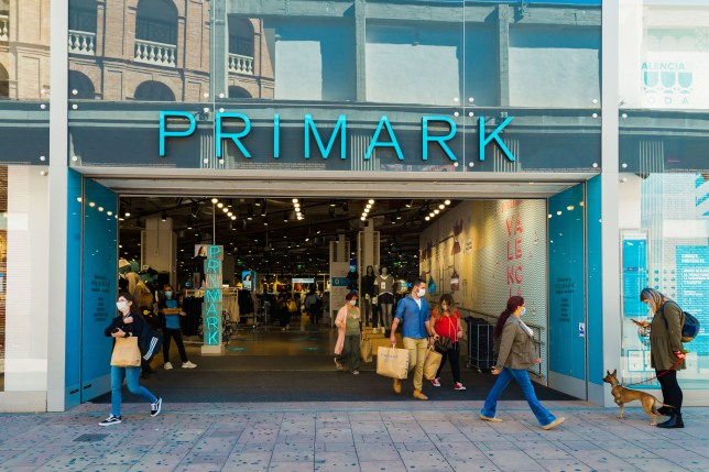 People wearing face masks walk past a Primark store