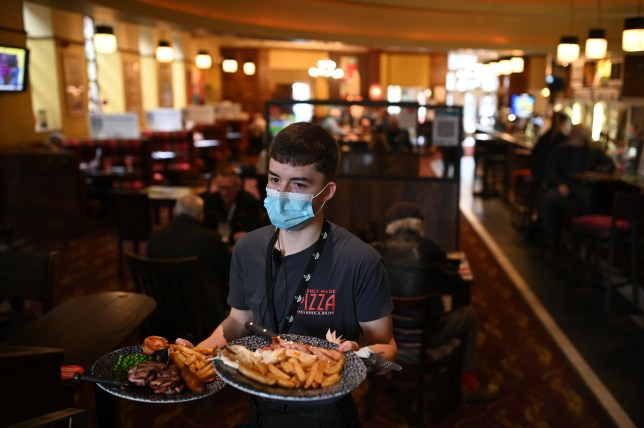 A member of the bar staff serves food in a Wetherspoons pub in Leigh, Greater Manchester.