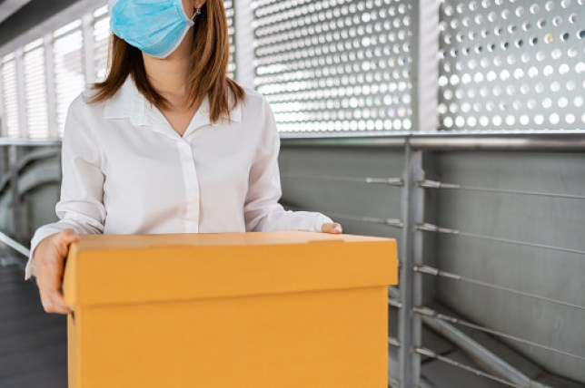 Woman carrying box out after losing job