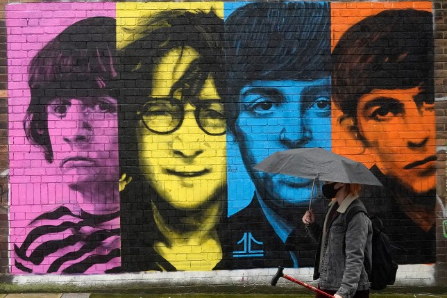 A person wearing a face mask walks past a Beatles memorial in Liverpool.