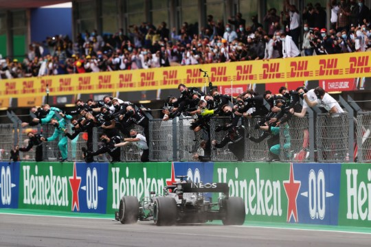 Mercedes team members celebrate on the pit wall as Lewis Hamilton crosses the finish line