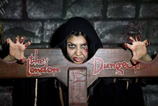 A woman covered in fake blood in stocks at the London Dungeons.