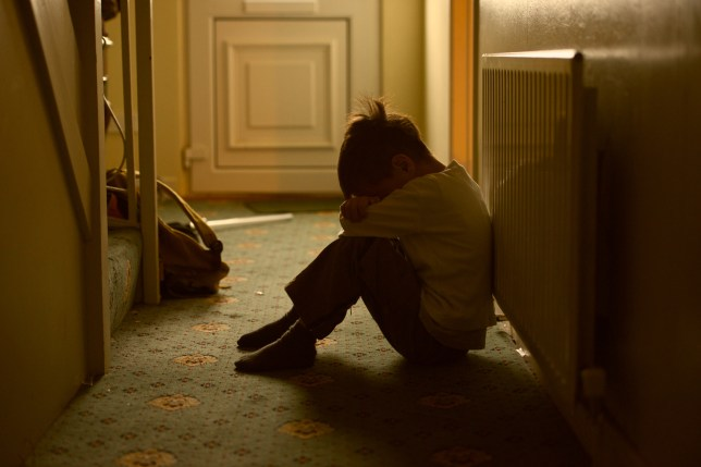 A child sitting with his head in his hands looking upset in the hallway of a dimly-lit home.