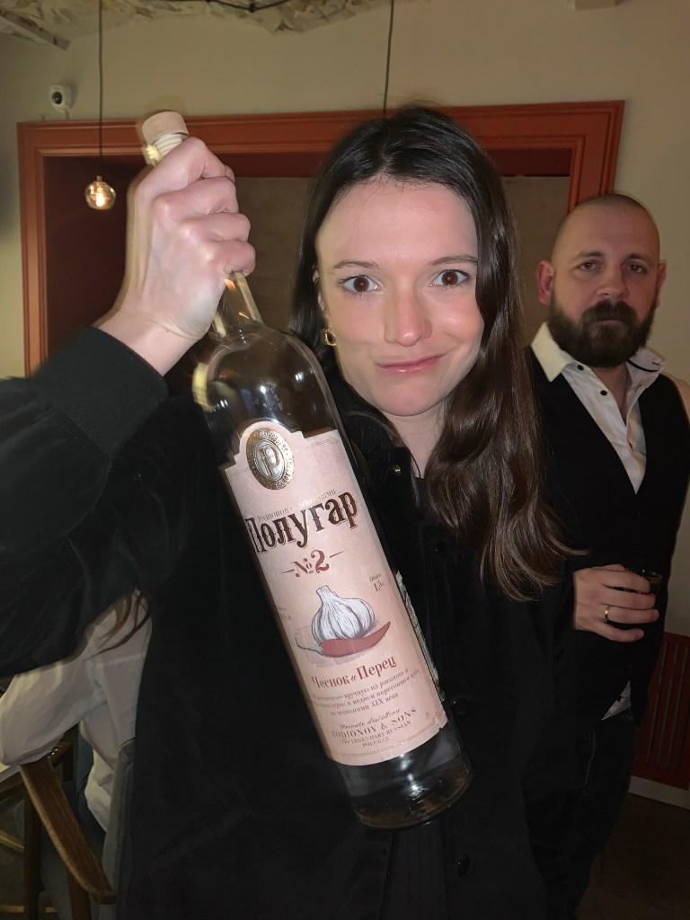 A woman holding a large bottle of garlic vodka.