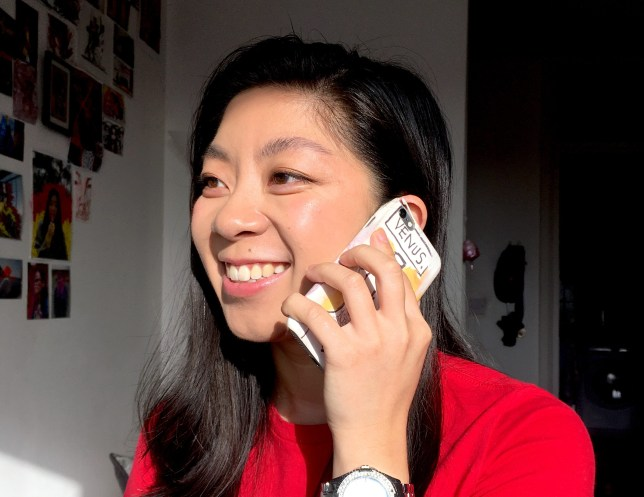 A woman wearing a red t-shirt is smiling while holding a phone to her ear