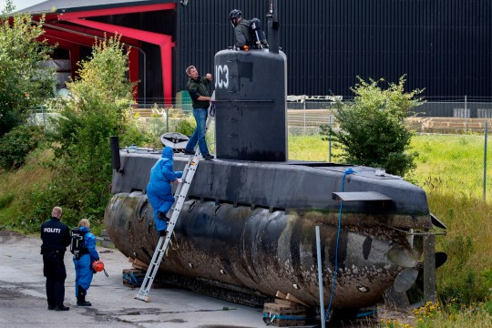 police technicians board Peter Madsen's submarine UC3 Nautilus on a pier in Copenhagen harbour, Denmark