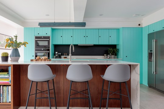 Kitchen island with grey chairs and turquoise cupboards