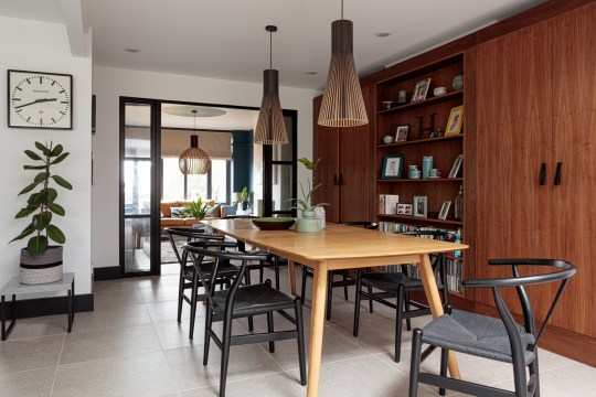 Wooden dining table with black modern chairs